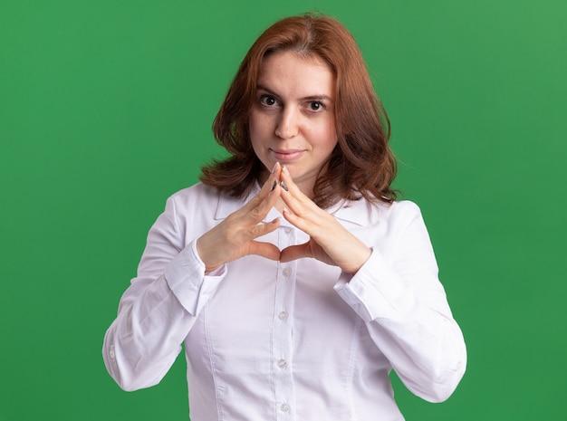 Jonge vrouw in wit overhemd hand in hand samen met sceptische glimlach kijken naar staande over groene muur