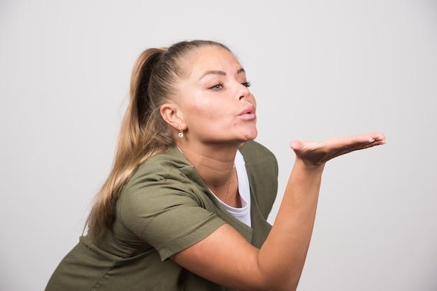 Jonge vrouw in wit overhemd kussen geven.