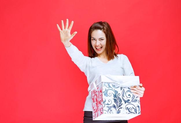 Jonge vrouw in wit overhemd met een bedrukte geschenkdoos en groet iemand