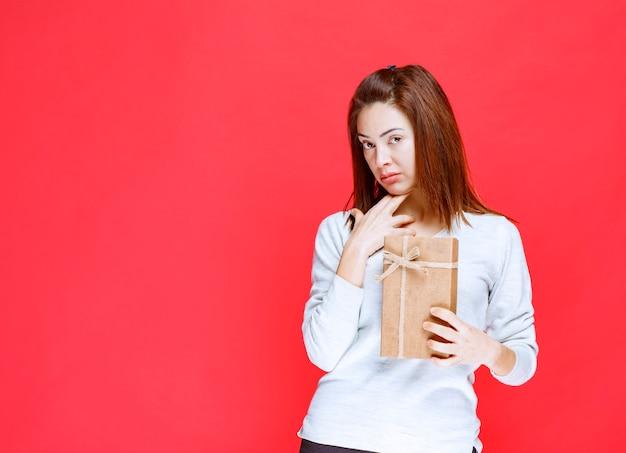 Jonge vrouw in wit overhemd met een kartonnen geschenkdoos en ziet er verward en attent uit