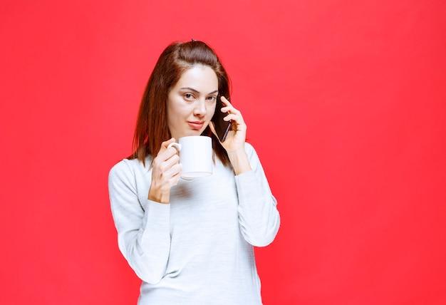 Jonge vrouw in wit overhemd met een witte koffiemok en een zwarte smartphone en praat met de telefoon