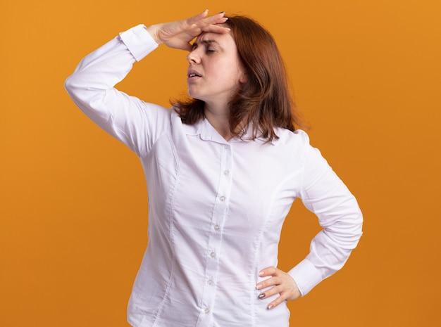 Jonge vrouw in wit overhemd met hand op haar hoofd moe en verveeld staande over oranje muur