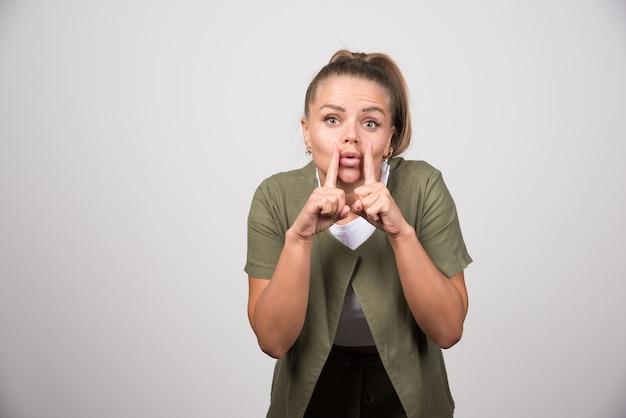 Jonge vrouw in wit overhemd steekt haar mond.