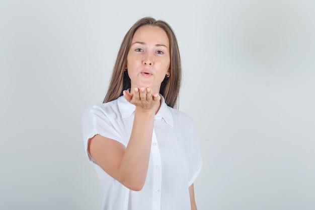 Jonge vrouw in wit overhemd waait luchtkus en kijkt vriendelijk