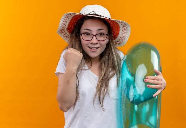 Jonge vrouw in wit t-shirt die de zomerhoed draagt die opblaasbare ring met balde vuist houdt die opgewekt en gelukkig status over oranje muur kijkt