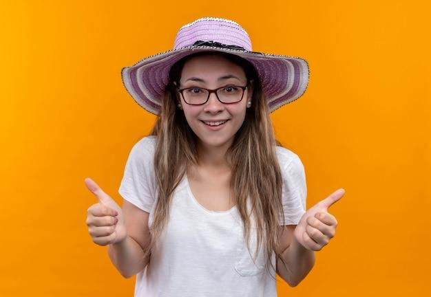 Jonge vrouw in wit t-shirt die de zomerhoed draagt die vrolijk glimlachend duimen toont die zich over oranje muur bevinden