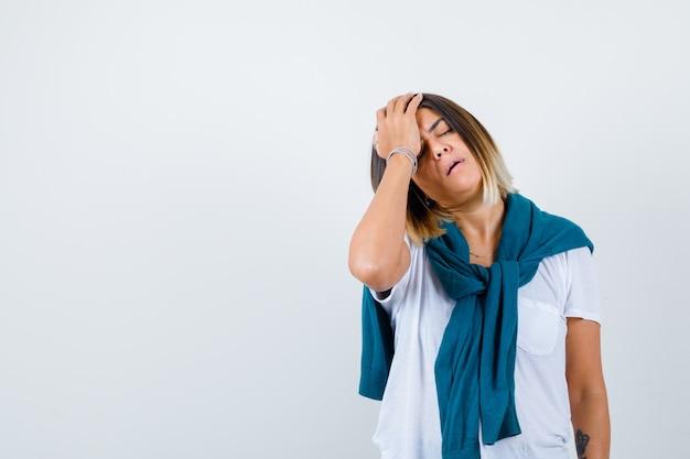 Jonge vrouw in wit t-shirt die het hoofd met de hand vasthoudt en er pijnlijk uitziet, vooraanzicht.