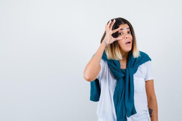 Jonge vrouw in wit t-shirt die ogen opent met vingers en nieuwsgierig kijkt, vooraanzicht.