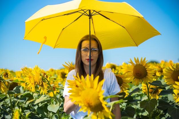 Jonge vrouw in wit t-shirt en glazen onder een gele paraplu op een zonnebloemgebied.