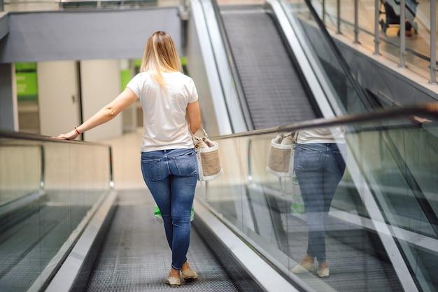 Jonge vrouw in wit t-shirt en jeans op roltrap in winkelcentrum. winkelen en plezier. levensstijl. het dagelijkse leven in de stad. goederen en consumptie.