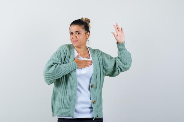 Jonge vrouw in wit t-shirt en mintgroen vest met hand op borst terwijl ze haar hand opsteekt om te begroeten en er gelukkig uit te zien