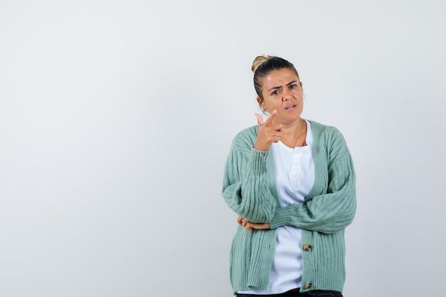 Jonge vrouw in wit t-shirt en mintgroen vest staande in denkende pose en peinzend kijkend