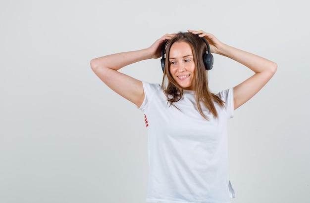 Jonge vrouw in wit t-shirt hand in hand op koptelefoon en op zoek blij