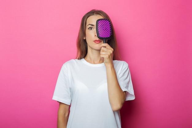 Jonge vrouw in wit t-shirt heeft betrekking op haar gezicht met kam op roze.