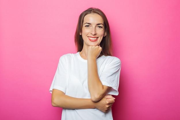 Jonge vrouw in wit t-shirt houdt hand onder de kin