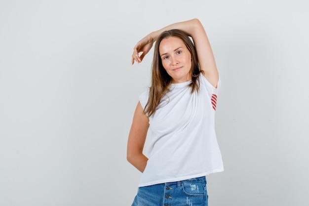 Jonge vrouw in wit t-shirt, korte broek arm boven het hoofd uitrekken en glimlachen
