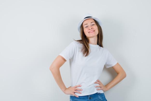 Jonge vrouw in wit t-shirt, korte broek, hoed poseren terwijl staande en op zoek zelfverzekerd.