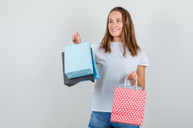 Jonge vrouw in wit t-shirt, korte broek met papieren zakken terwijl ze wegkijkt en vrolijk kijkt