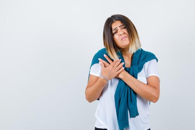 Jonge vrouw in wit t-shirt met handen op de borst en somber kijkend, vooraanzicht.
