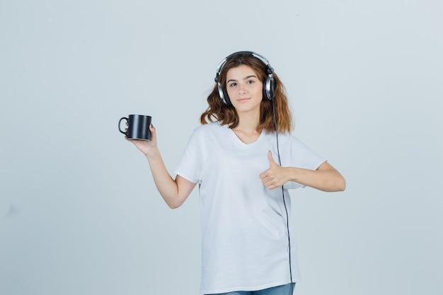 Jonge vrouw in wit t-shirt met kopje drank, duim opdagen en op zoek vrolijk, vooraanzicht.