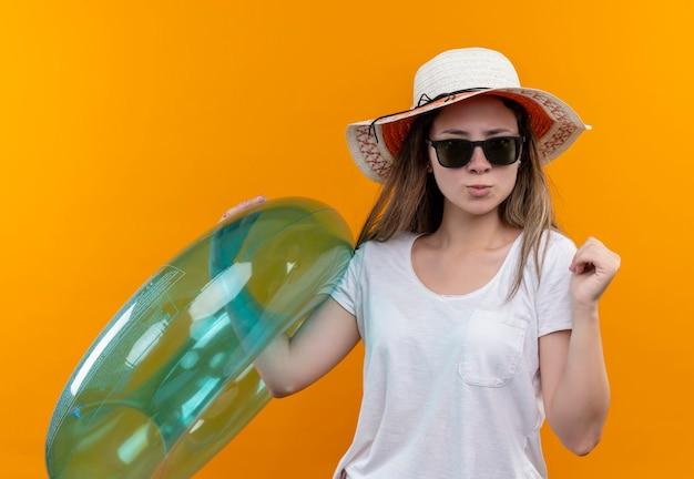 Jonge vrouw in wit t-shirt met zomerhoed die opblaasbare ring met balde vuist houdt die zelfverzekerd met ernstige uitdrukking over oranje muur kijkt