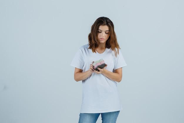 Jonge vrouw in wit t-shirt, spijkerbroek kijken naar geschenkdoos en aarzelend, vooraanzicht op zoek.