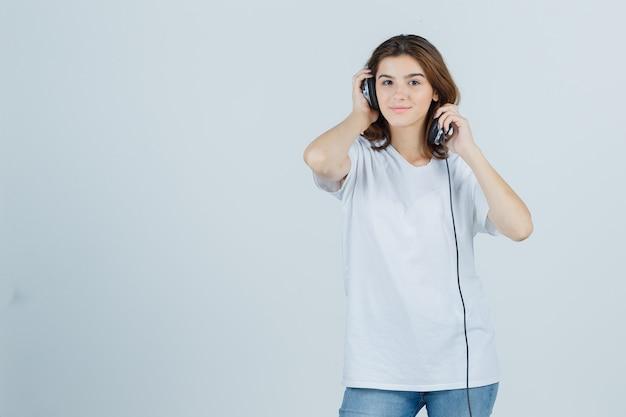 Jonge vrouw in wit t-shirt, spijkerbroek koptelefoon opstijgen en op zoek dromerig, vooraanzicht.