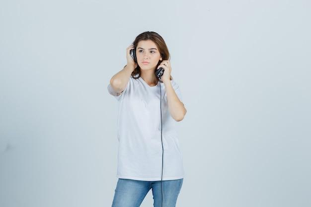 Jonge vrouw in wit t-shirt, spijkerbroek koptelefoon opstijgen en peinzend, vooraanzicht kijken.