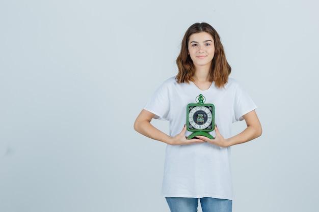 Jonge vrouw in wit t-shirt, spijkerbroek met klok en op zoek vrolijk, vooraanzicht.