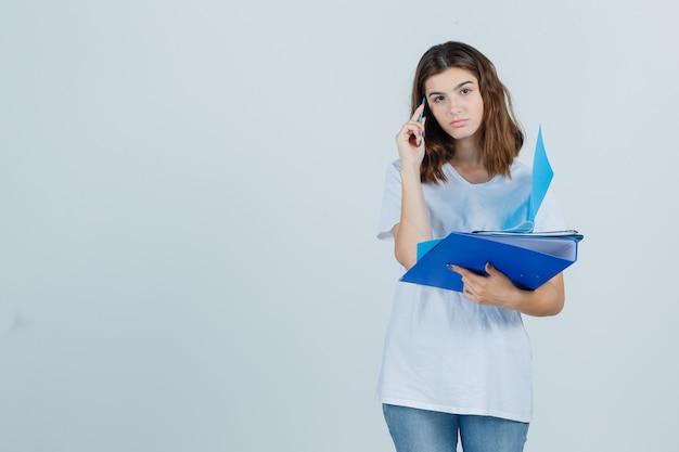 Jonge vrouw in wit t-shirt, spijkerbroek met mappen en pen en op zoek peinzend, vooraanzicht.