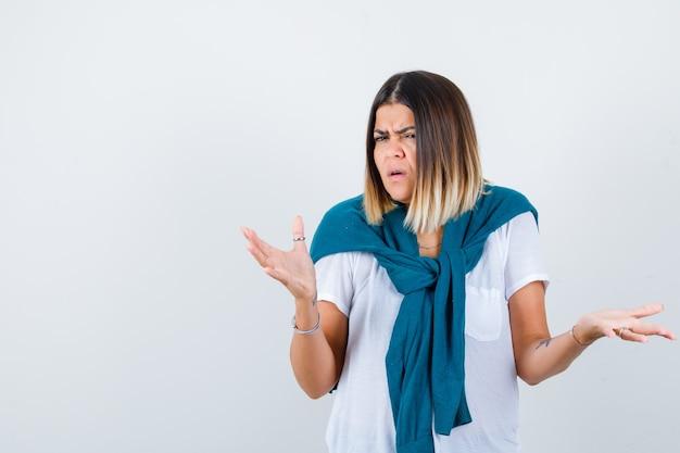 Jonge vrouw in wit t-shirt spreidt armen en kijkt haatdragend, vooraanzicht.