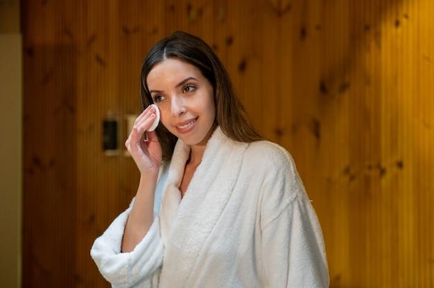 Jonge vrouw in witte badjas gezicht huid met wattenschijfje en cosmetisch product afvegen tijdens de dagelijkse schoonheidsprocedure in de badkamer