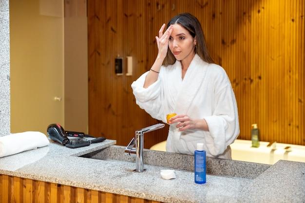 Jonge vrouw in witte badjas staande voor spiegel in de badkamer en cosmetische crème op gezicht toe te passen tijdens de dagelijkse huidverzorgingsroutine