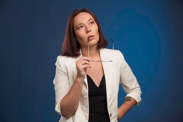 Jonge vrouw in witte blazer die optische oogglazen draagt.