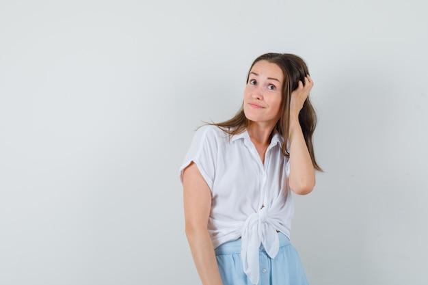 Jonge vrouw in witte blouse en lichtblauwe rok die hoofd krabt en vrolijk kijkt