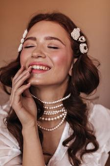 Jonge vrouw in witte blouse en pareljuwelen lacht. momentopname van vrouw met sproeten op beige achtergrond.