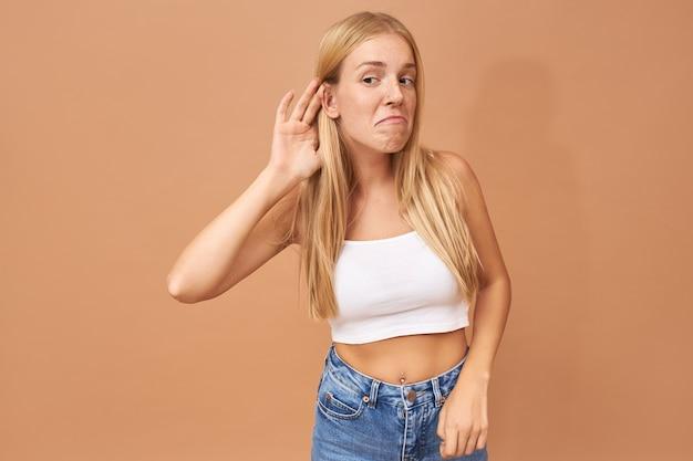 Jonge vrouw in witte bovenkant en spijkerbroek die hand bij haar oor houdt, aandachtig luisterend