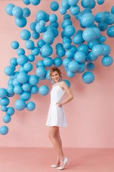 Jonge vrouw in witte cocktail jurk die zich voordeed op roze muur achtergrond met blauwe bubbels