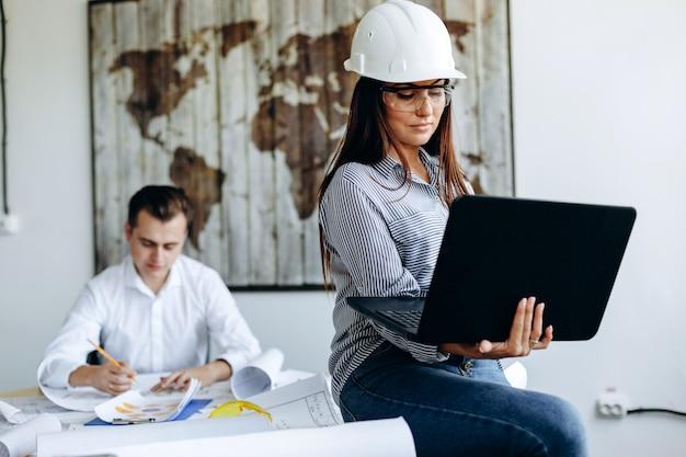 Jonge vrouw in witte helm in kantoor werken op laptop