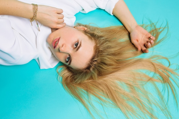 Jonge vrouw in witte hoody op blauwe achtergrond. mooie meid