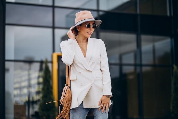 Jonge vrouw in witte jas buiten lopen