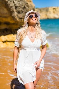 Jonge vrouw in witte jurk, hoed en zonnebril wandelen op het rotsachtige strand