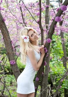 Jonge vrouw in witte jurk in de lentepark