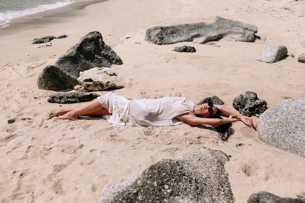 Jonge vrouw in witte jurk liggend zand en geniet van zee op haar zomervakantie