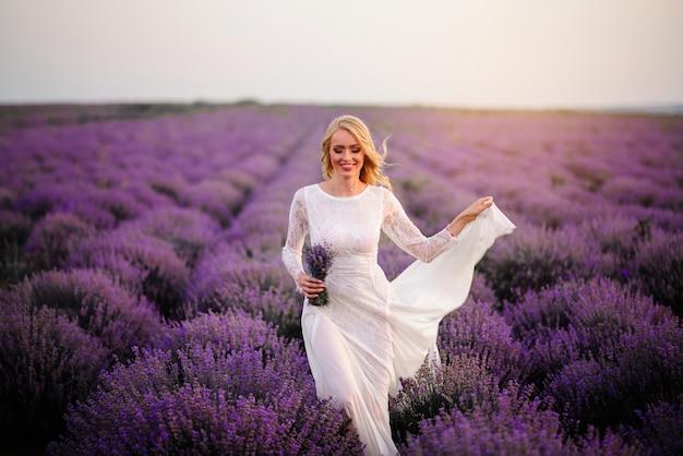 Jonge vrouw in witte jurk loopt door bloeiend lavendelveld bij zonsondergang