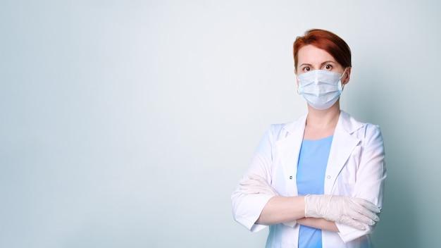 Jonge vrouw in witte medische jurk en beschermend masker staat met haar armen gevouwen op haar borst