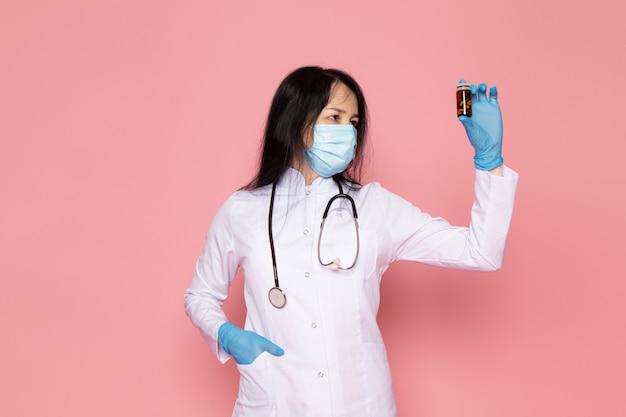 Jonge vrouw in witte medische pak blauwe handschoenen blauw beschermend masker met kleurrijke pillen op roze