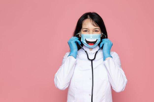 Jonge vrouw in witte medische pak blauwe handschoenen blauw beschermend masker met stethoscoop op roze