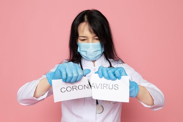 Jonge vrouw in witte medische pak blauwe handschoenen blauw beschermend masker met stethoscoop scheurend coronavirus woord op roze