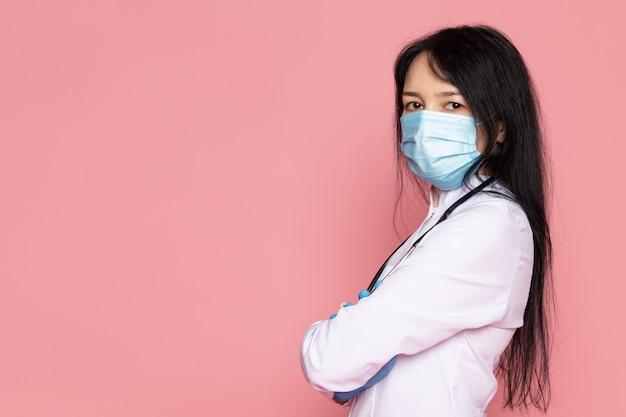 Jonge vrouw in witte medische pak blauwe handschoenen blauw beschermend masker op roze